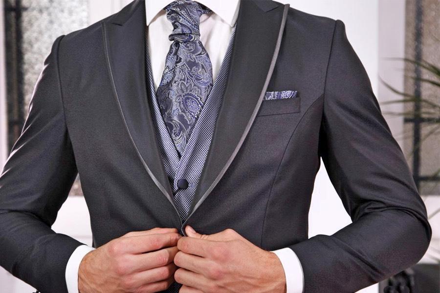 Traje de novio en negro, con detalles en azul pardo.